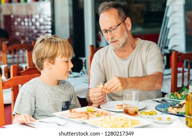 Family in the restaurant, father and son eating shrimps, summer vacation by the sea