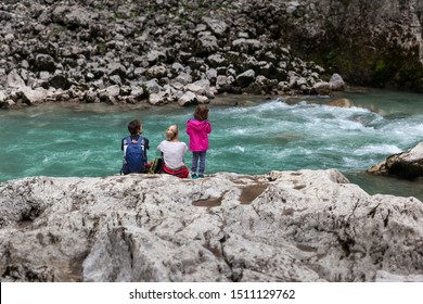 family resting after trekking on the rocks on the bank of a wild mountain river
