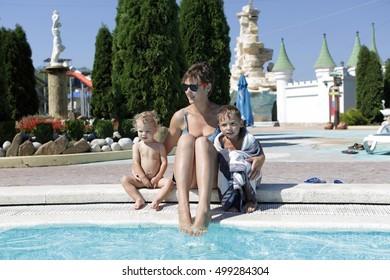 Family resting on edge of pool in aquapark