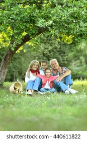 Family resting in park with apples