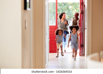 Family Returning Home From Shopping Trip Using Plastic Free Grocery Bags Opening Front Door