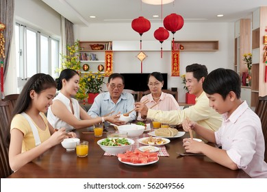 Family reunion dinner for Tet celebration at home; couplets with best wishes for coming year in the background