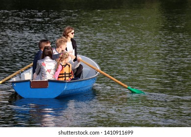 Family rides in rowing boat on a lake in Izmailovo park. Parents with children having fun, leisure on a water - Moscow, Russia, May 2019