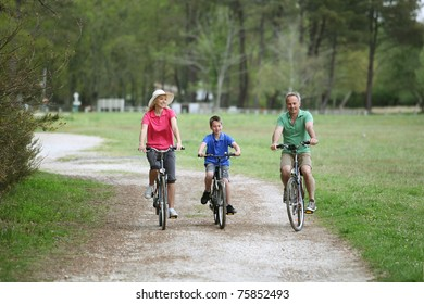 Family riding bicycles in countryside