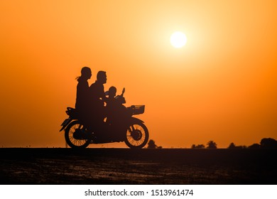 Family riding a motorcycle on sunset background, silhouetted