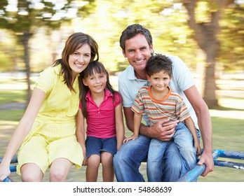 Family Riding On Roundabout In Park