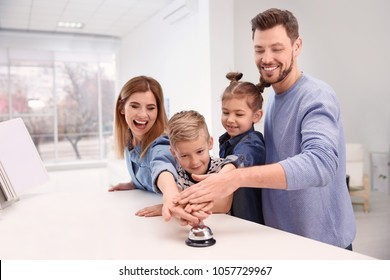 Family ringing service bell on reception desk in hotel