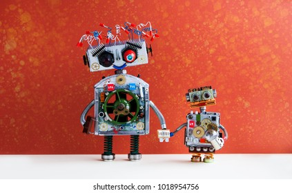 Family robots. Big robot mom holds the hand of a small child robot. Creative design futuristic cyborg toys on red wall background