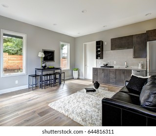 Family room design with wet bar nook. Furnished with black leather sofa and glass coffee table atop white fluffy rug. Northwest, USA