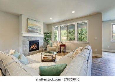 Family room interior features grey linen sectional lined with colorful pillows facing fireplace with grey tile surround across from glass top coffee table atop white soft rug. Northwest, USA