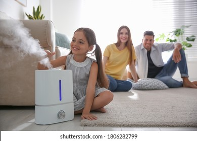 Family in room with modern air humidifier