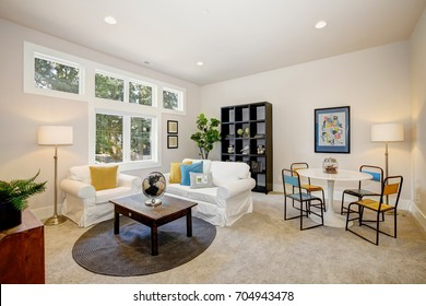 Family room and playroom features play table, white slipcovered sofa and armchair adorned with bright yellow and blue pillows facing wooden cocktail table with a globe on the top. Northwest, USA
