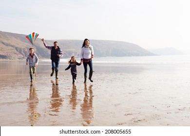 Family Running Along Winter Beach Flying Kite