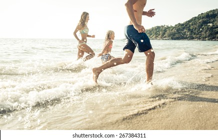 family running out the water in phuket, Thailand. Concept about family, vacation, fun and people