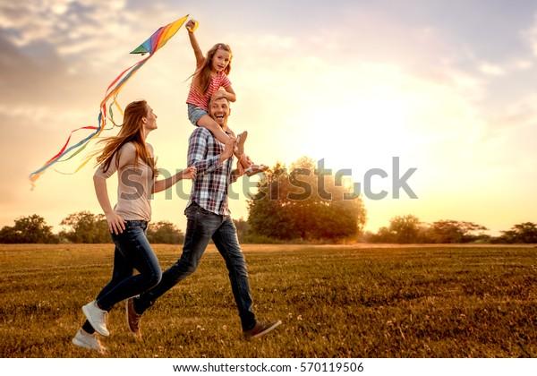 Familie, die durch das Feld fliegt und Drachenfliegen lässt
