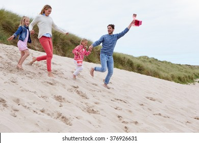 Family Running Through Sand Dunes Together
