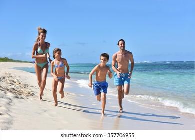 Family runnning on a sandy beach in Caribbean island