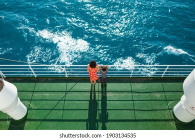 The family is sailing on a cruise ship, a mother with  son are standing at the fence on the ship and looking at the sea, traveling by ferry, a boy with mom are sailing on a ship.