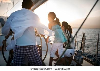 Family sailing at sunset
