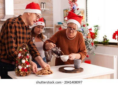 Family with santa hat celebrating christmas holiday together in xmas decorated culinary kitchen eating baked cookies, drinking coffee. Grandchild enjoying winter holiday during christmastime
