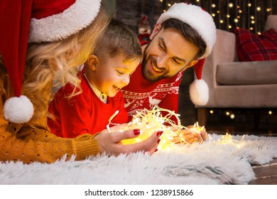 Family in santa hats with child kid boy playing with light christmas garland in warm red sweaters lying on floor at decorated home near Christmas tree. Merry Christmas and Happy 2019 New Year concept,