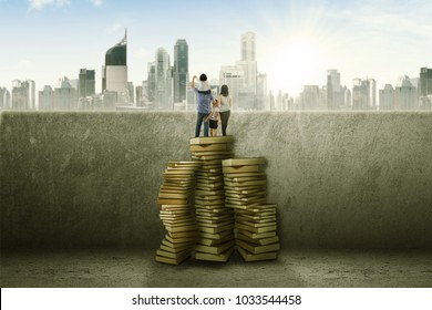 Family savings concept: Young family with little kid standing on Stack of books looking to the future
