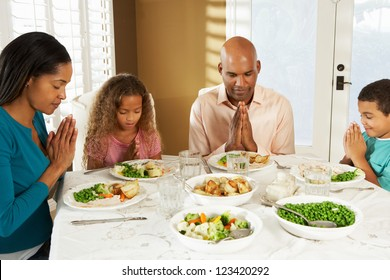 Family Saying Grace Before Meal At Home