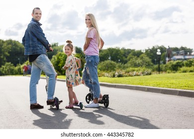 Family with scooters in the park