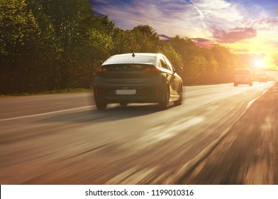 A family sedan car driving fast on the countryside asphalt road with trees against night sky with sunset