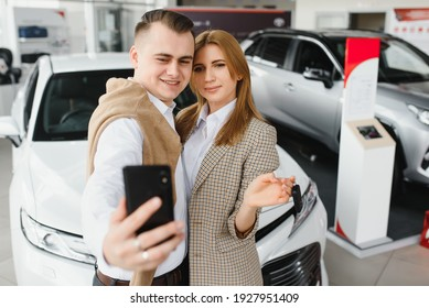Family selfie in dealership. Happy young couple chooses and buying a new car for the family.