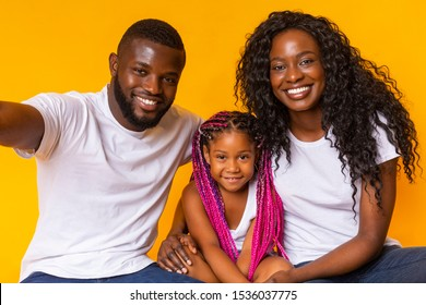 Family selfie. Happy african american guy taking photo with his daughter and wife, posing over yellow studio background.