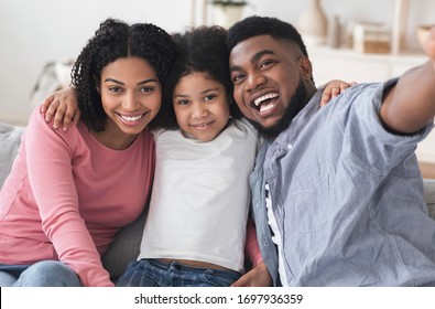 Family Selfie. Joyful Black Man Taking Photo With His Wife And Daughter At Home, Posing To Camera Together, Closeup
