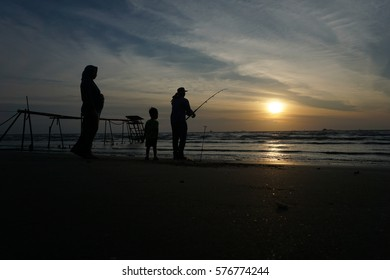 Family in semi silhouette on beach. A father, fisherman holding his rod, while his wife and son accompanying him.