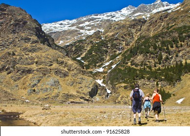 Family with senior parents and a young daughter hiking in the mountains