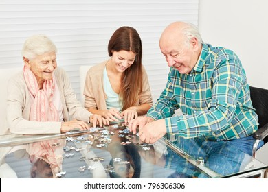 Family with seniors and granddaughter have fun playing puzzle at home