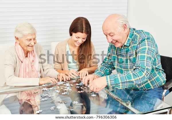 Familie mit Senioren und Enkelin haben zu Hause viel Spaß beim Puzzlespielen