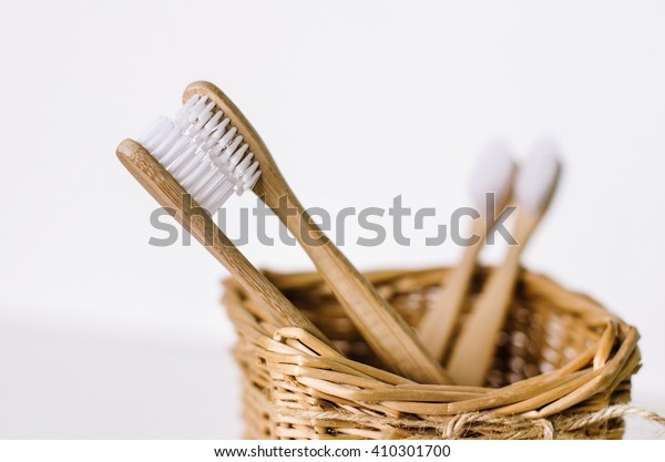 Un conjunto familiar de cuatro cepillos de bambú de madera en una cesta de paja. Dos cepillos de dientes son como padres enamorados besándose y enfocándose, y otros dos - son como niños y borrosos