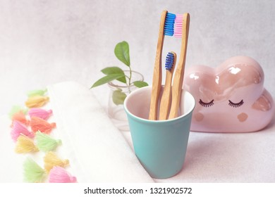 A family set of three mom, dad and son wooden bamboo toothbrushes on white background with colourful towel