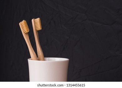 Family set of two natural wood bamboo toothbrushes in glass on black background. Plastic free essentials teeth care. Sustainable lifestyle.
