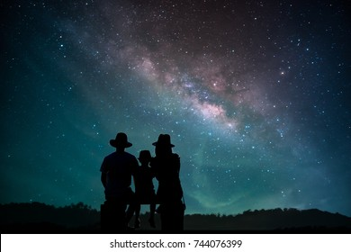 The family shadow, three parents, travelers, children sat watching the Milky Way on the sky on a romantic night.