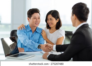 Family shaking hands with real estate broker after successful deal