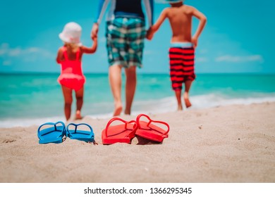 family shoes and father with kids walking at beach