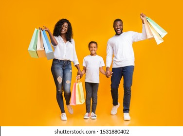 Family Shopping. African American Parents And Their Daughter Carrying Shopper Bags And Smiling Over Yellow Background, Copy Space