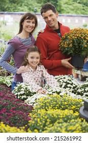 Family shopping for flowers in garden centre, man holding pot plant, smiling, portrait