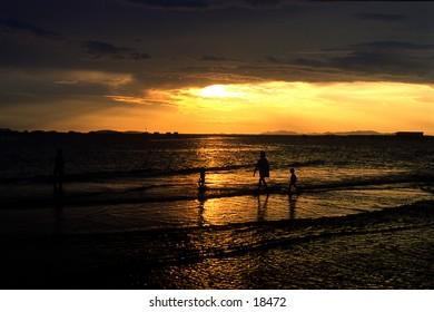 A family shot in silhouette quietly walking along enjoying a sunset on a beach in Tela, Honduras.