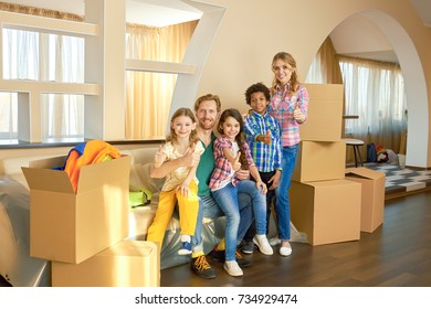 Family showing thumbs up indoor. Happy people and carboard boxes.