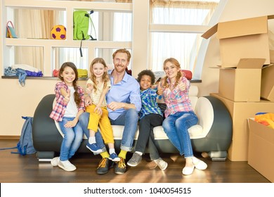 Family showing thumbs up, boxes. Happy people indoors. Get apartment without credit.