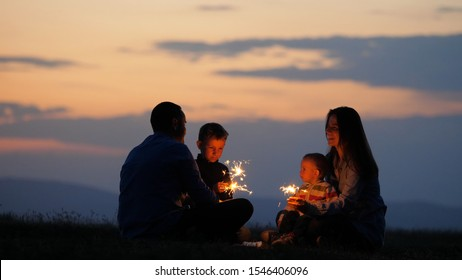 Family silhouette holding firework sparklers in their hands, joy in front of sunset sky