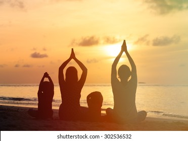 family silhouettes doing yoga at sunset sea