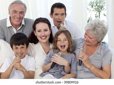 Family singing karaoke with microphones in living-room
